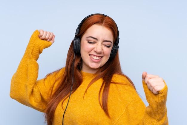 Garota adolescente ruiva sobre música e parede azul isolada ouvindo e dançando