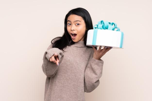 Garota adolescente segurando um bolo grande isolado em bege surpreso e apontando a frente