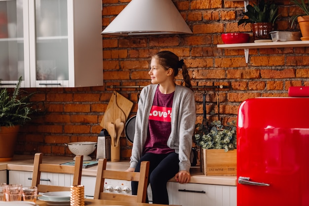Garota adolescente sentado na cozinha. cozinha em estilo loft com paredes de tijolos e geladeira vermelha.