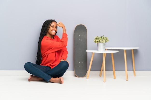 Garota adolescente skatista afro-americana com cabelo trançado, sentada no chão fazendo forte gesto