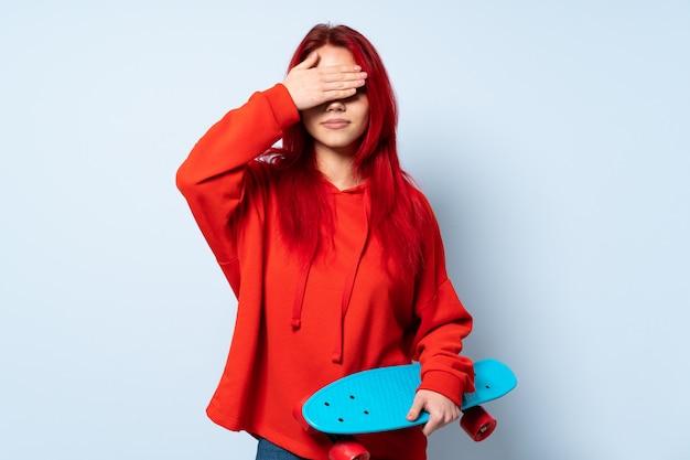 Garota adolescente skatista isolada na parede branca, cobrindo os olhos pelas mãos. não quero ver algo