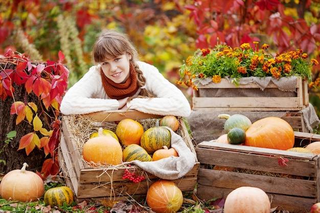Garota adorável adolescente com abóboras no parque outono. atividades de outono para crianças. dia das bruxas e diversão de tempo de ação de graças para a família.
