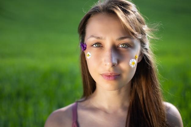 Garota adorável aplica flores silvestres e margaridas na pele do rosto como manchas
