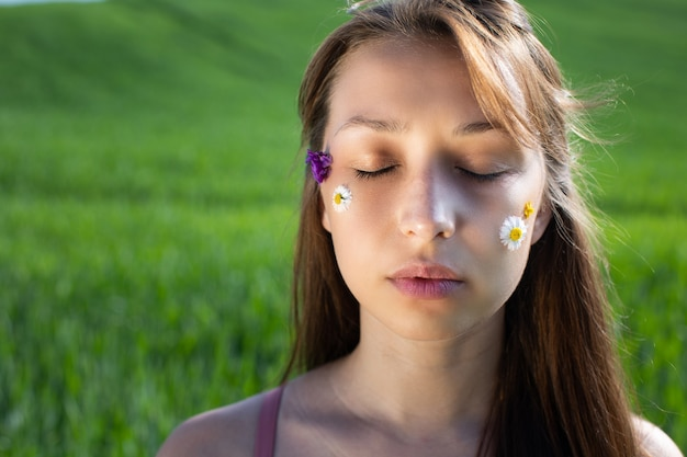 Garota adorável aplicando flores silvestres e margaridas