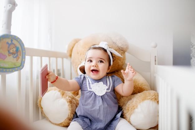 Garota adorável bebê no berço, brincando com o telefone inteligente.