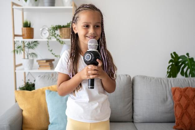 Garota adorável cantando ao microfone em casa