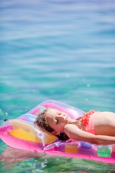 Garota adorável colchão de ar inflável no mar