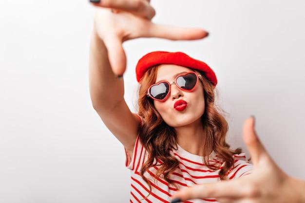 Garota adorável com batom vermelho posando. glamourosa francesa na boina, fazendo a expressão do rosto de beijo.