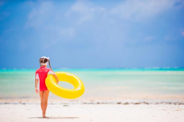 Garota adorável com círculo de borracha inflável vai nadar no mar
