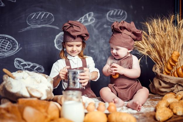 Garota adorável com criança na mesa de cozinha