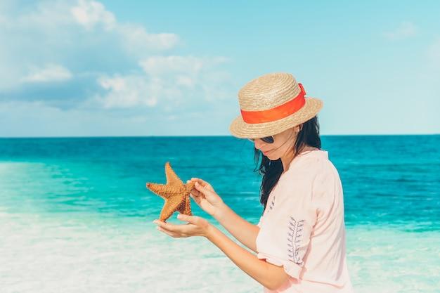 Garota adorável com estrela do mar na praia