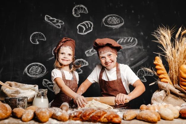 Garota adorável com irmão cozinhar