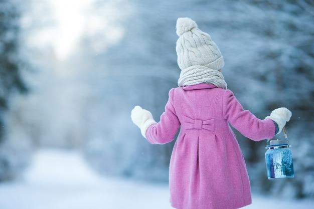 Garota adorável com lâmpada e vela no inverno na véspera de natal ao ar livre