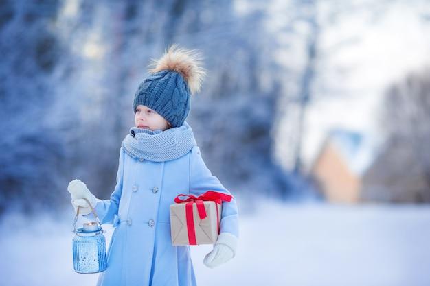 Garota adorável com presente de caixa de natal no inverno ao ar livre na véspera de natal