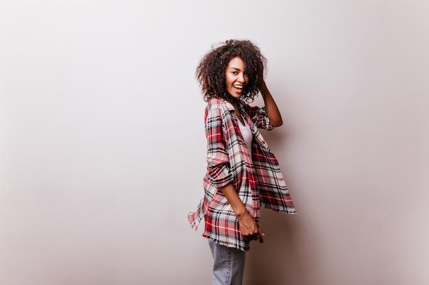 Garota adorável com roupa casual brincando brincando em branco. mulher africana bem torneada incrível de camisa vermelha sorrindo