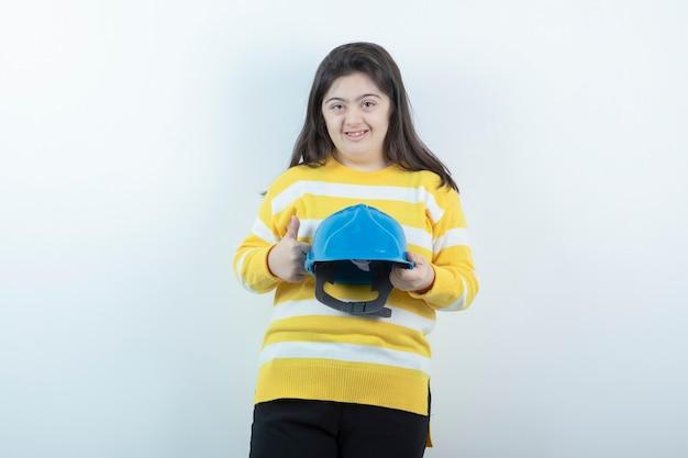 Garota adorável com suéter listrado segurando um capacete de segurança azul na parede branca