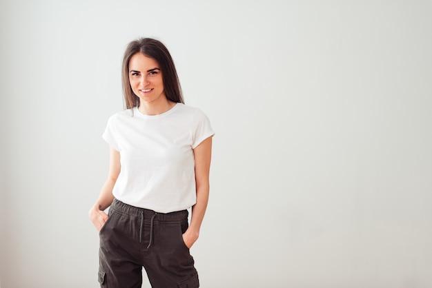 Garota adorável com um sorriso lindo em uma camiseta branca, mãos nos bolsos, sobre um fundo claro com um lugar em branco para texto