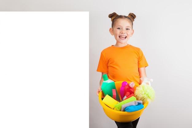 Garota adorável com uma bacia cheia de produtos de limpeza