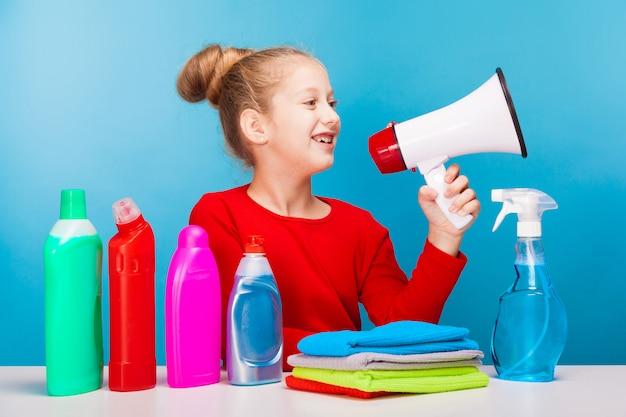 Garota adorável com vários produtos de limpeza segurando um alto-falante