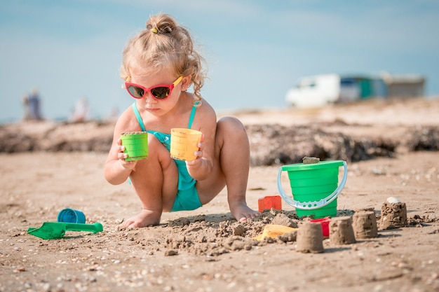 Garota adorável criança brincando na praia de areia branca