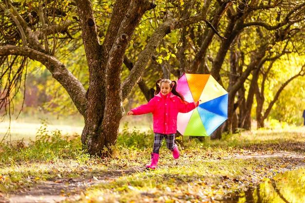 Garota adorável criança com guarda-chuva colorida ao ar livre no dia chuvoso de outono