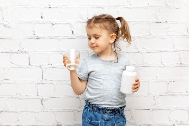 Garota adorável criança com um frasco de remédio branco e um copo d'água tomando comprimidos e vitaminas