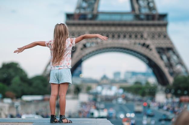 Garota adorável criança em paris na torre eiffel durante as férias de verão