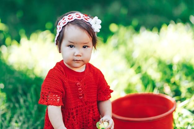 Garota adorável criança feliz com coroa de flores tricotada, vestindo um vestido vermelho, desfrutando de piquenique em um belo jardim de frutas florescendo