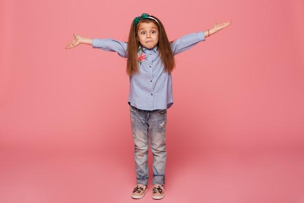 Garota adorável criança no aro de cabelo e roupas casuais, dando um enorme abraço com as mãos abertas enquanto sendo isolado contra a parede rosa