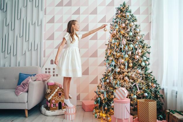 Garota adorável decora a árvore de natal dentro de casa. boas festas de natal