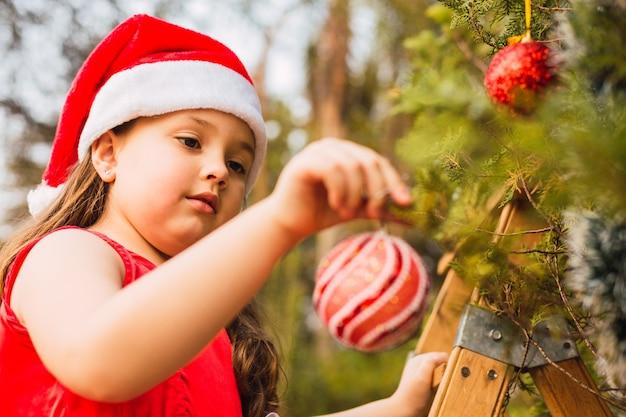 Garota adorável decorando a árvore de natal