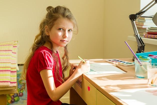Garota adorável desenha aquarela na mesa em casa