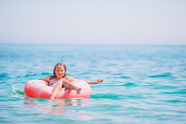 Garota adorável em colchão inflável de ar no mar