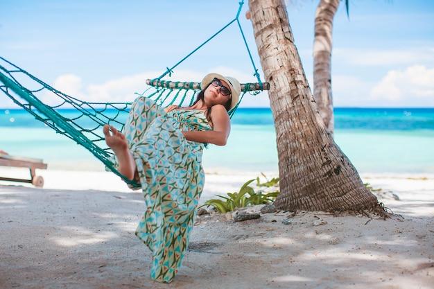 Garota adorável em férias tropicais relaxando em uma rede