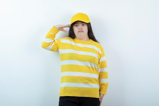 Garota adorável em um suéter listrado com tampa amarela em pé na parede branca