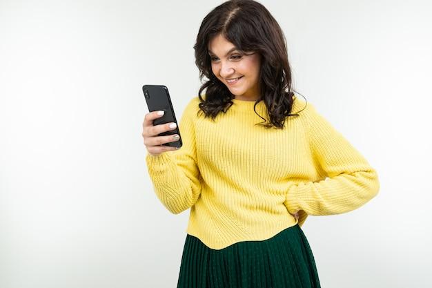 Garota adorável em uma blusa amarela, sorrindo, espreita uma mensagem no telefone em um fundo branco
