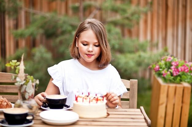 Garota adorável feliz comendo bolo de aniversário no terraço do café. criança de 10 anos comemora aniversário.
