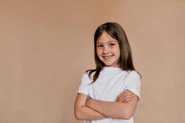Garota adorável feliz vestindo camiseta branca posando sobre parede bege.