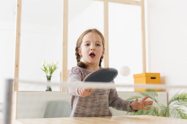 Garota adorável jogando tênis de mesa dentro de casa