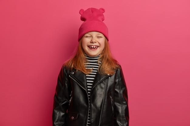 Garota adorável ruiva estilosa ri com sinceridade, fecha os olhos, fica muito contente, alegra-se com o bom dia, passando o tempo livre com a mãe e o pai, usa chapéu rosa e jaqueta de couro, se prepara para a escola