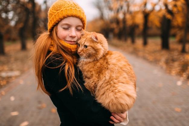 Garota adorável sardas com expressão de rosto gentil, segurando seu gato vermelho em um vale do parque outono
