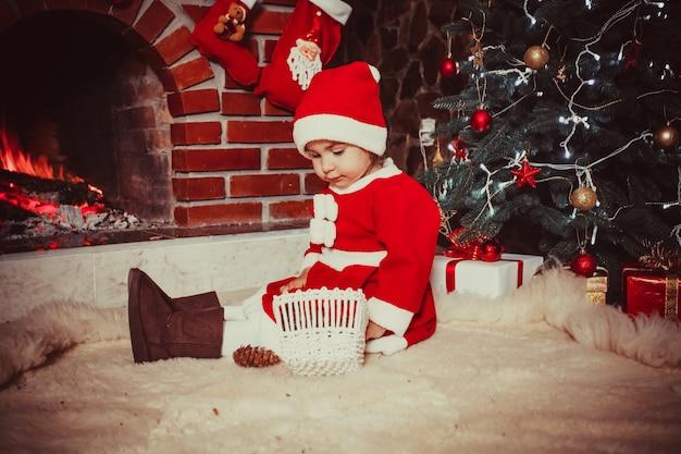 Garota adorável sentada perto da lareira e brincando com cones - decorações de natal