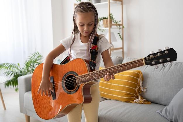 Garota adorável tocando violão em casa