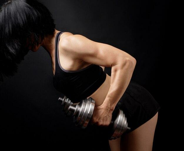 Garota adulta com cabelo preto está vestida com um sutiã esportivo e shorts curtos está fazendo exercícios físicos