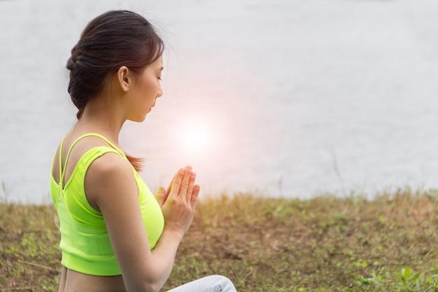 Garota adulta jovem fazendo pose de ioga no lado do rio
