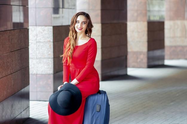 Garota adulta turista está sentado em uma mala