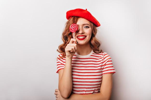 Garota afável na boina vermelha, posando com pirulito. um sonho francês modelo feminino em pé na parede branca com doces.