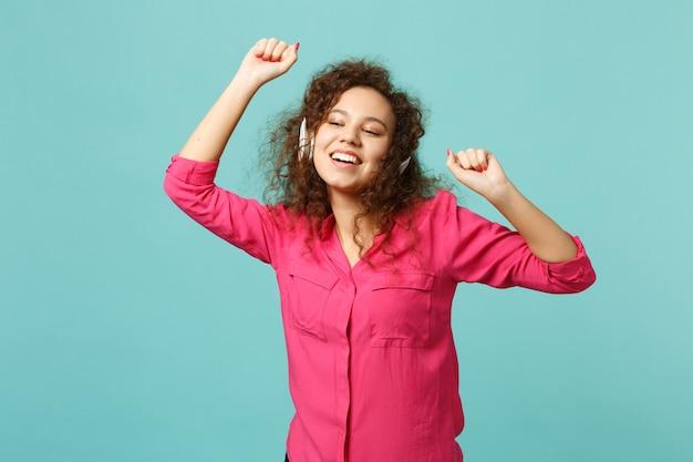 Garota africana atraente em roupas casuais rosa, ouvindo música com fones de ouvido e dançando isolado no fundo da parede azul turquesa. emoções sinceras de pessoas, conceito de estilo de vida. simule o espaço da cópia.