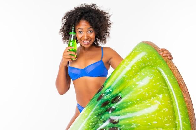 Garota africana atraente em um maiô azul separado detém um colchão de natação e bebe um cocktail na parede branca
