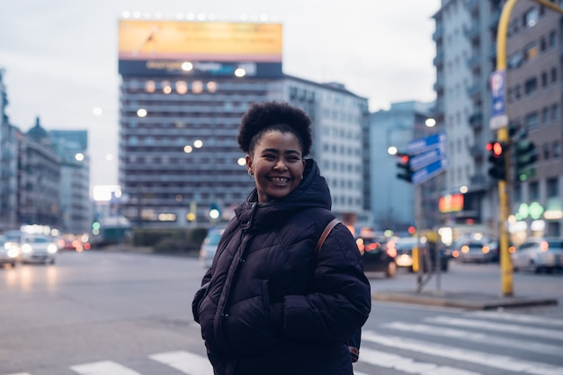 Garota africana e encaracolada sorrindo na rua